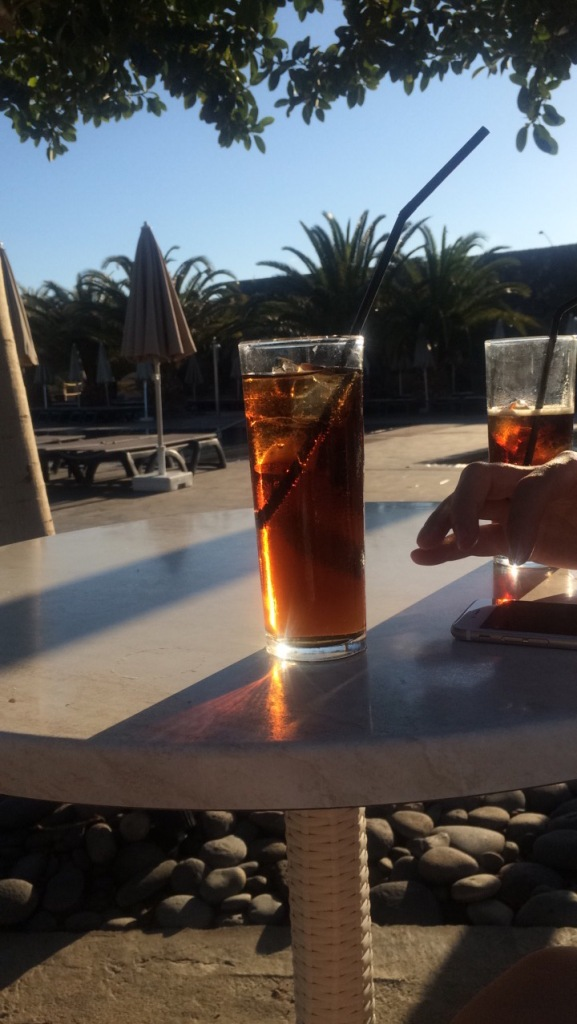 Two drinks on a table with palm trees in the background at a holiday resort in Tenerife.