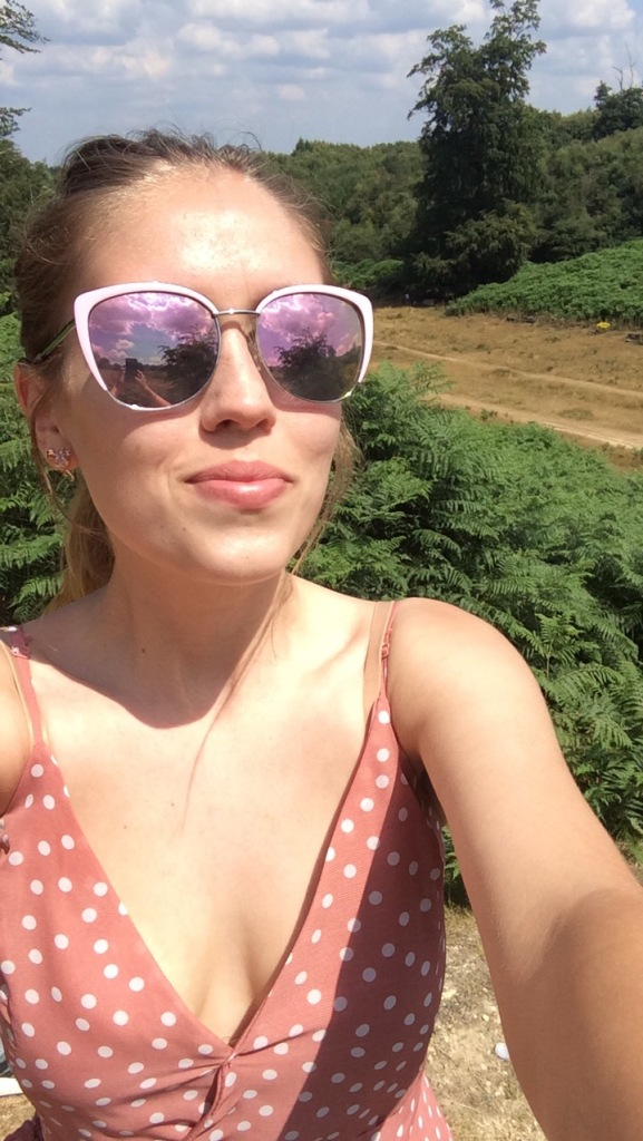 A selfie on a woman in a pink polka dot dress, wearing pink sunglasses. With a view of a park in the background