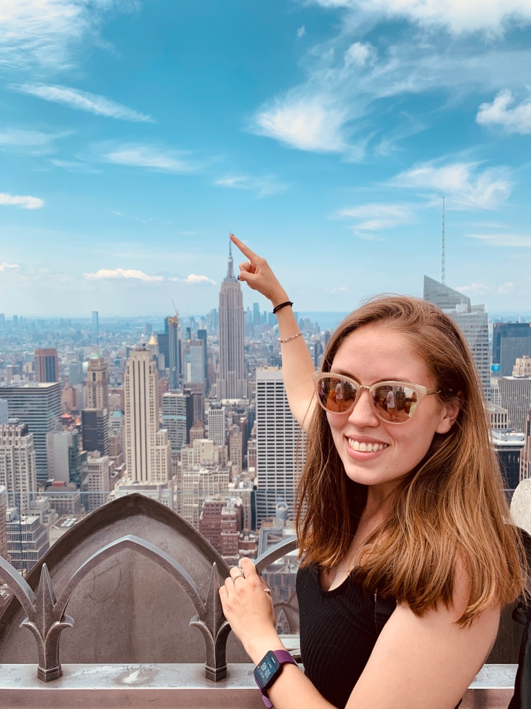 A woman pretending to touch the top of the Empire state building from the viewing deck of the Rockefeller Centre.
