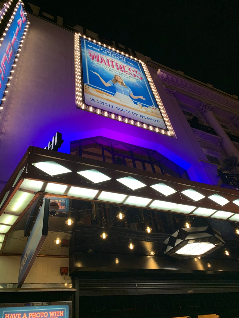 "The lit up sign of the musical ""Waitress"" outside the building where the performance occurs in London."