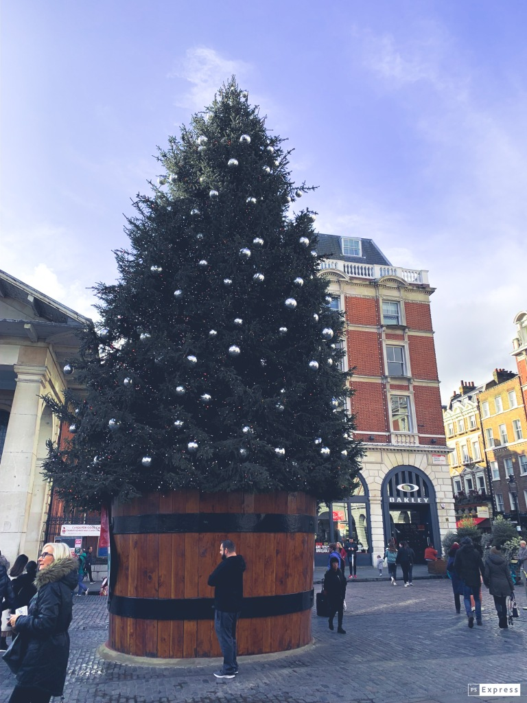 The Christmas tree during the day in Covent garden. A huge tree with silver baubles on in a wooden bucket with black around the top.