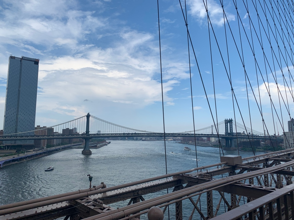 A view of New York from Brooklyn Bridge looking out to another bridge and the water.