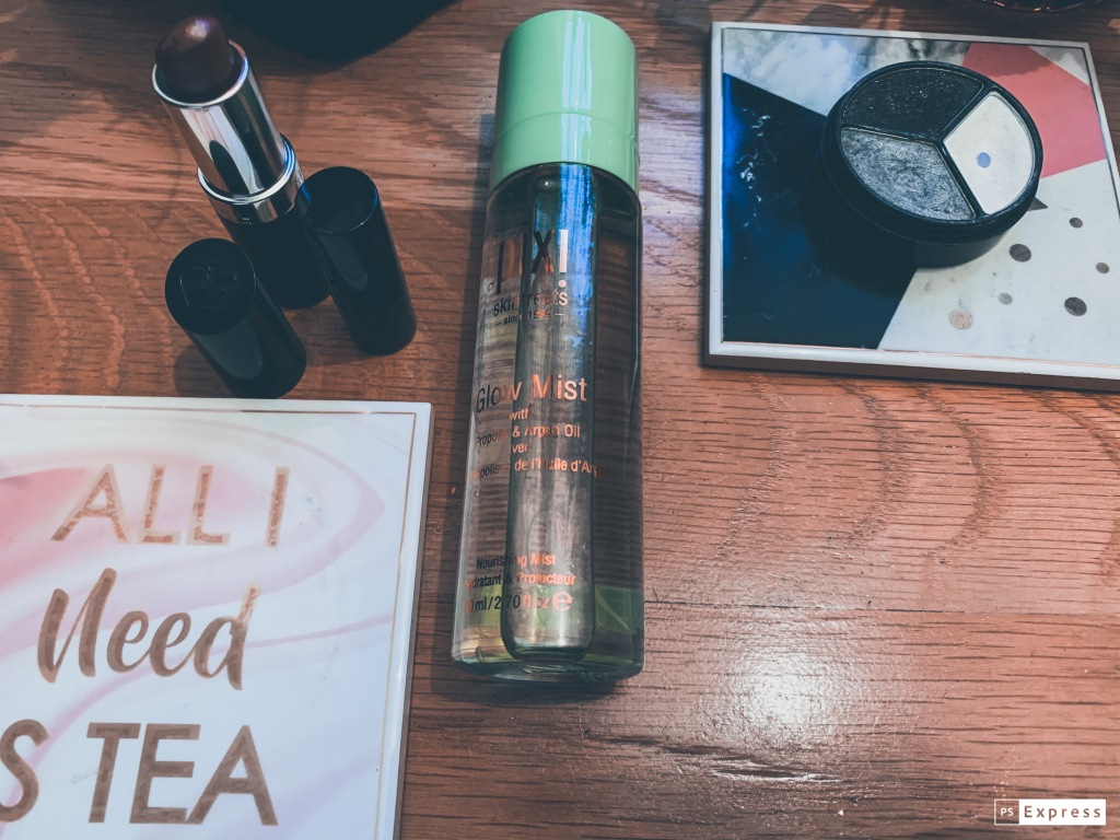 "A flatlay of different make up products including; Pixi glow mist, a brown colour lipstick and an eye shadow pot with three colours; black, white and a grey shimmer. All next to a placemat with ""All I need is tea"" on it."