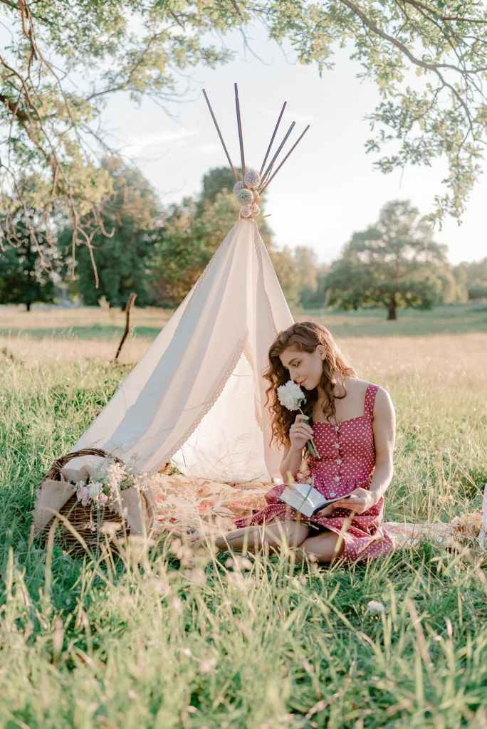 A woman smelling a white flower sitting on the grass in front of a tipi with a wooden wicker basket, in a field with trees.