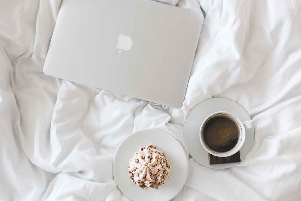 A flatlay angle of an apple mac laptop, a coffee and a cake on a plate all white.