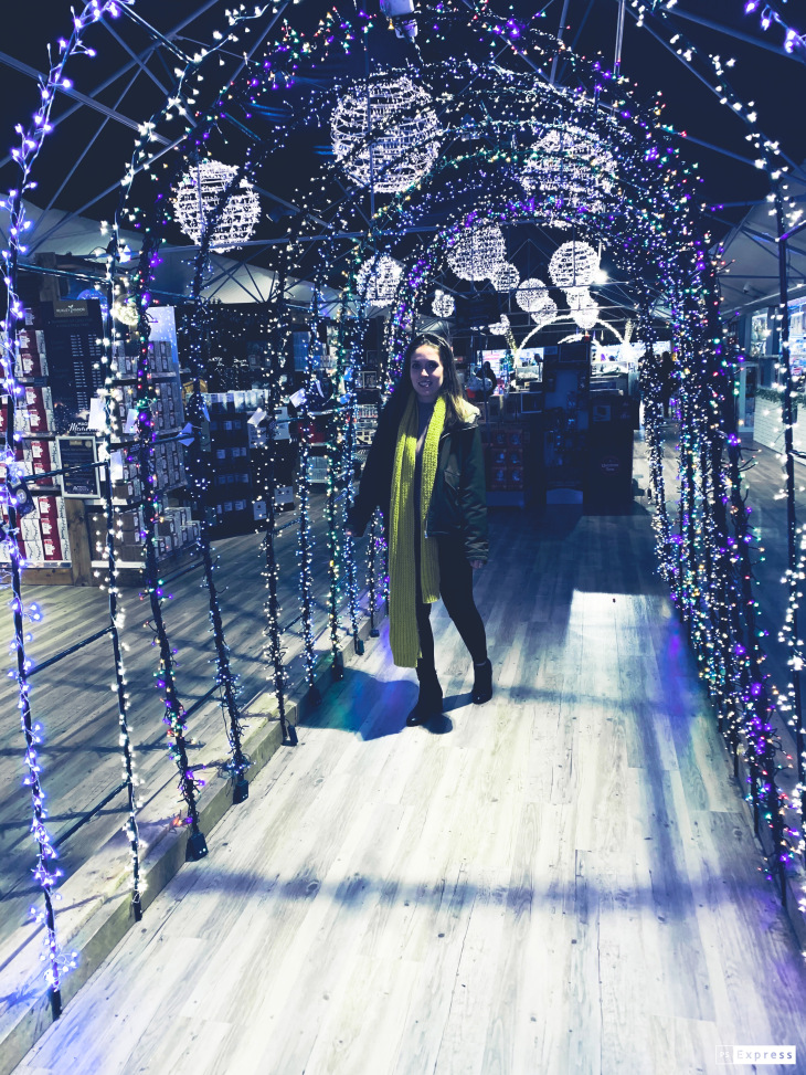 A woman walking through a tunnel of fairy lights in a christmas store