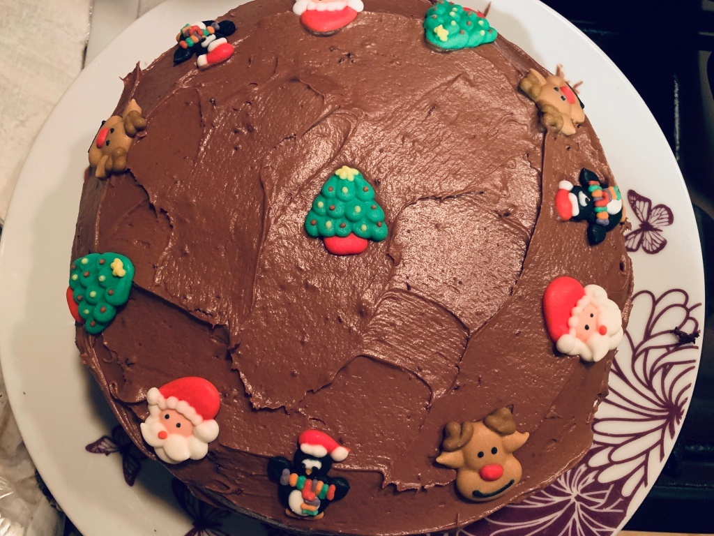 Top view of a choclate cake with chocolate icing and tiny icing decorations featuring a tree, santa, penguin and a reindeer.
