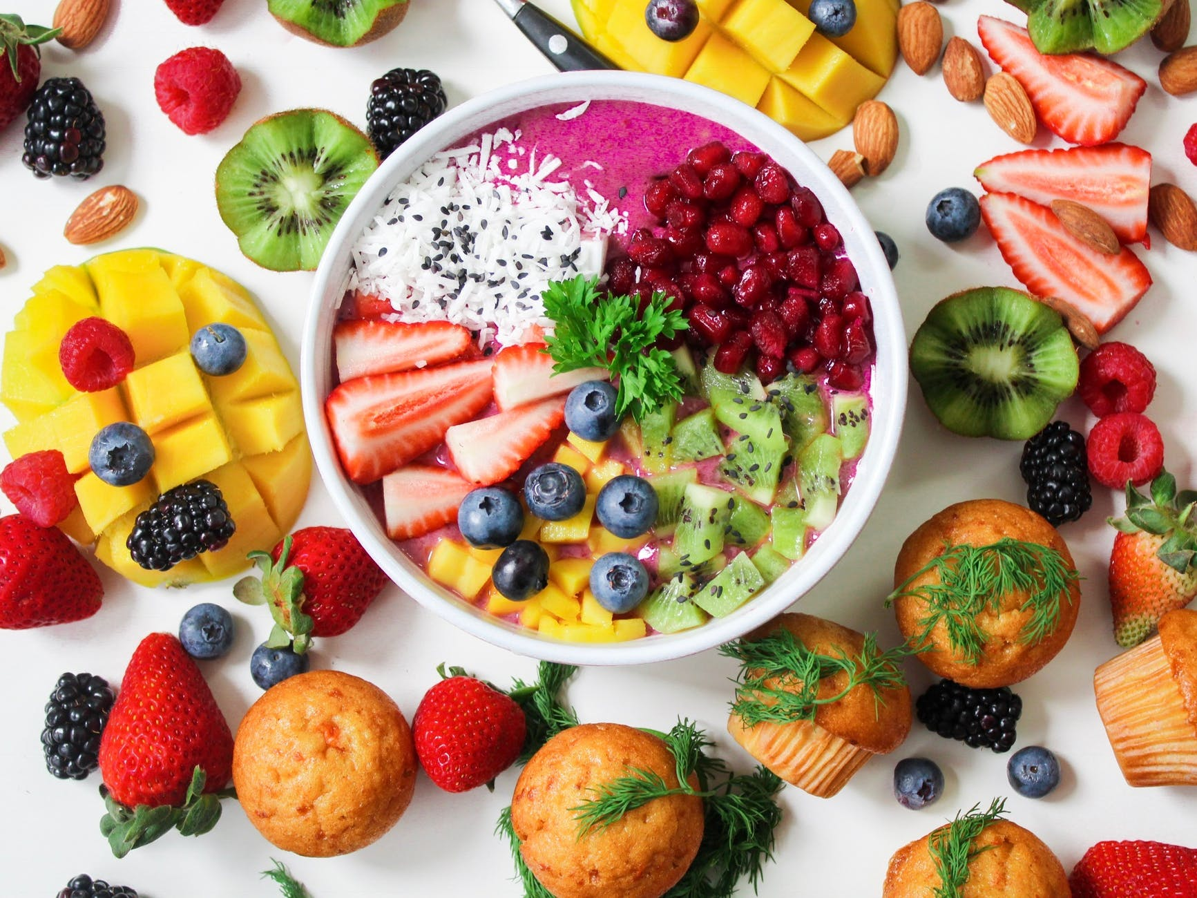 A selection of fruit on a table surrounding a bowl of selection of fruit. Also some muffins