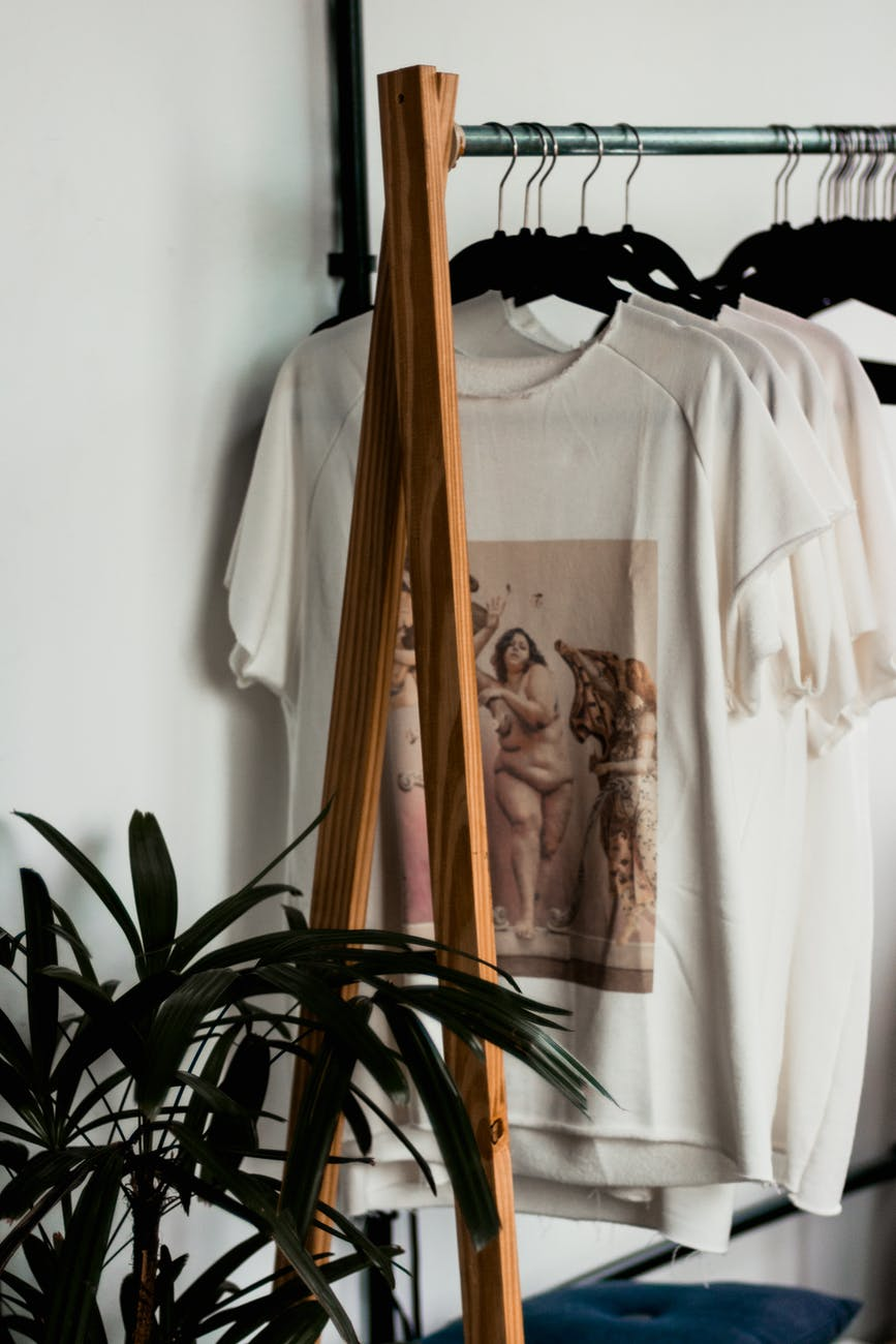 A capsule wardrobe of clothes hanging on a wooden and metal clothes rack. With a green plant next to it.