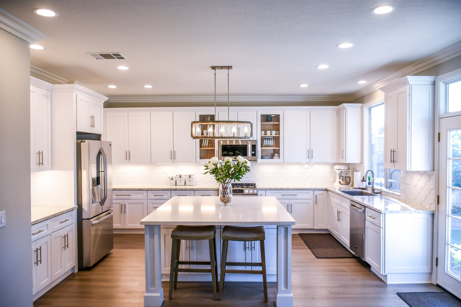 A huge kitchen with an Island that has two stools at the end. There are flowers placed on the Island. The whole kitchen has a clean white effect.