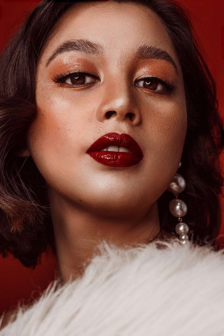 A close up of a woman wearing a dark red lipstick, and golden eye make-up