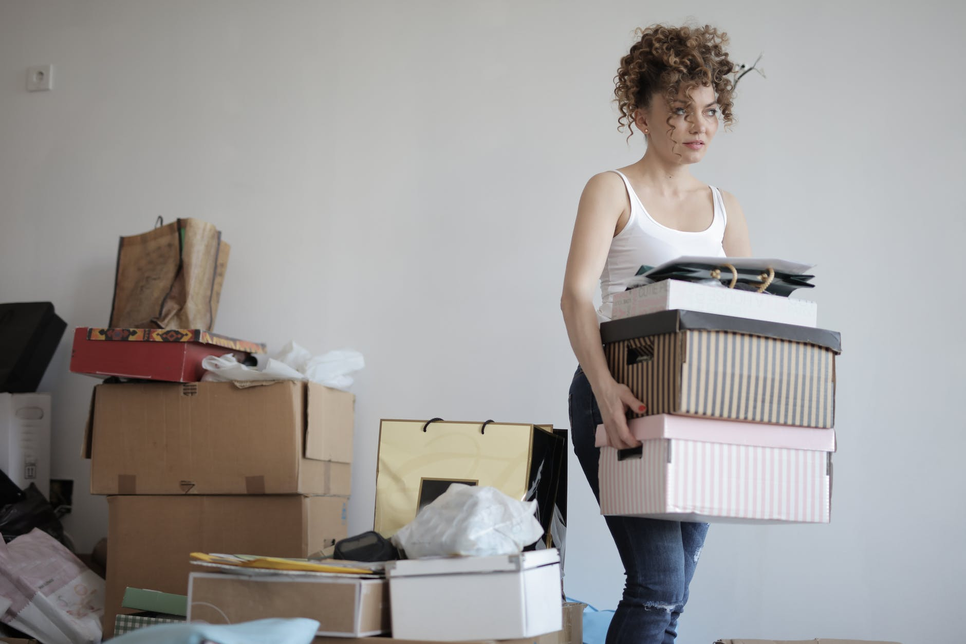 A woman holding three boxes next to a pile of other boxes.