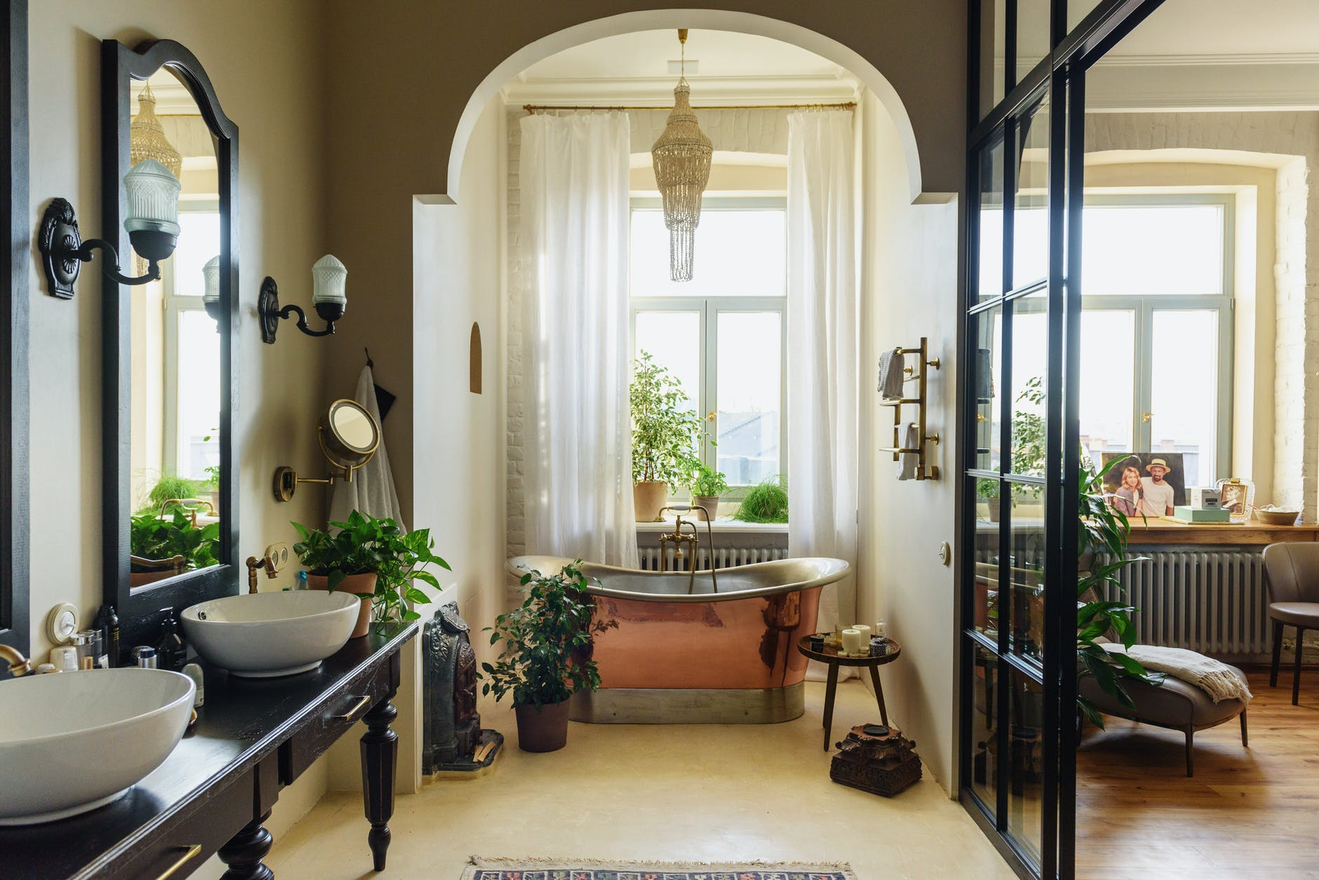 An urban looking bathroom, with a copper not fixed bath tub by a window.