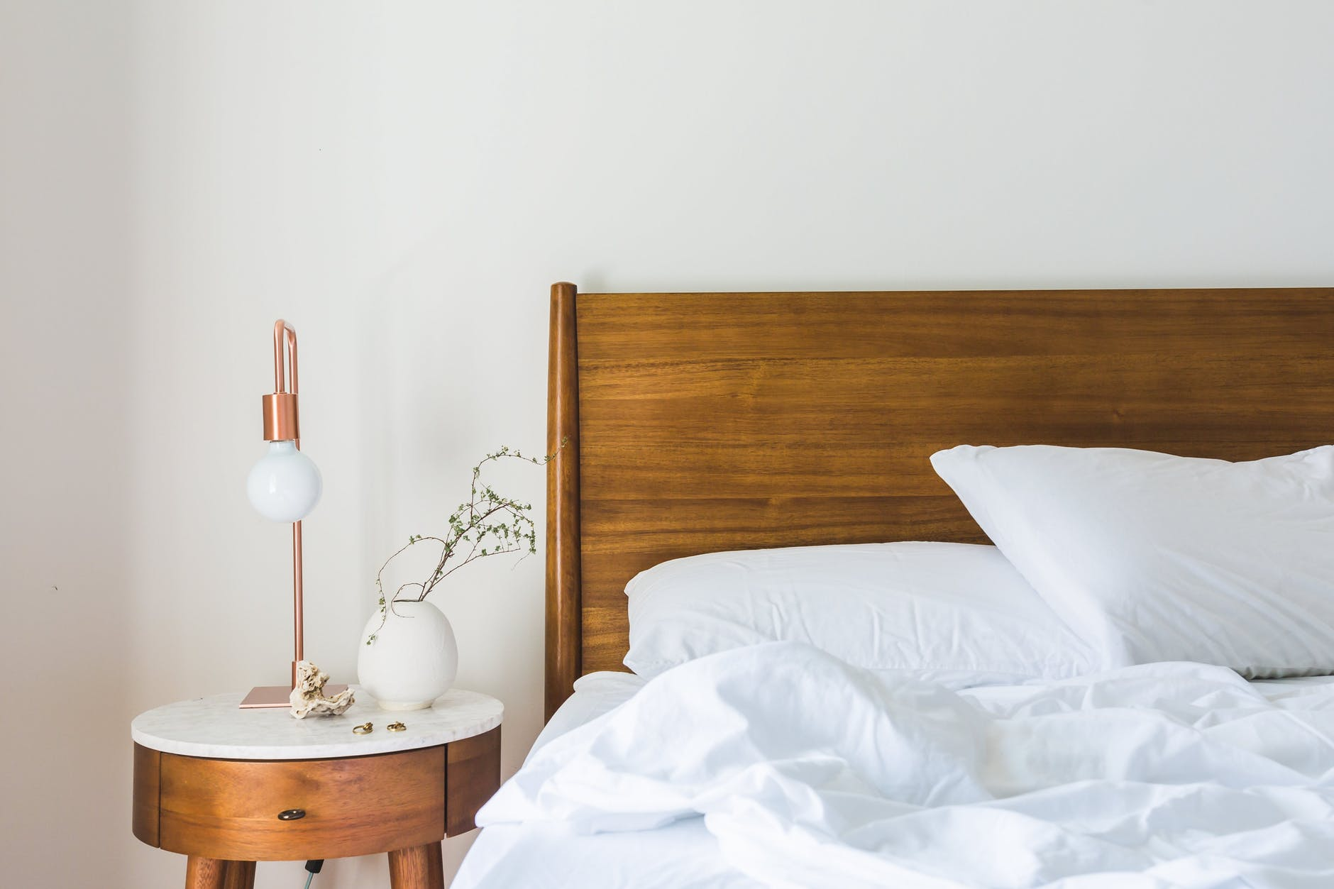 A bed and wooden headboard, with a side table that has a plant and lamp on it.
