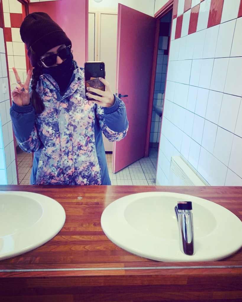 A woman doing a peace sign with sunglasses, a hat and a ski jacket on in the toilet on a ski resort.