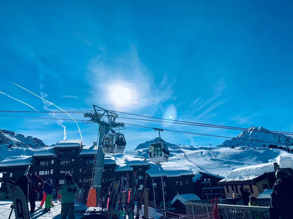 A view of a hotel and ski lift in the mountains in La Plagne in France with the sun shining.