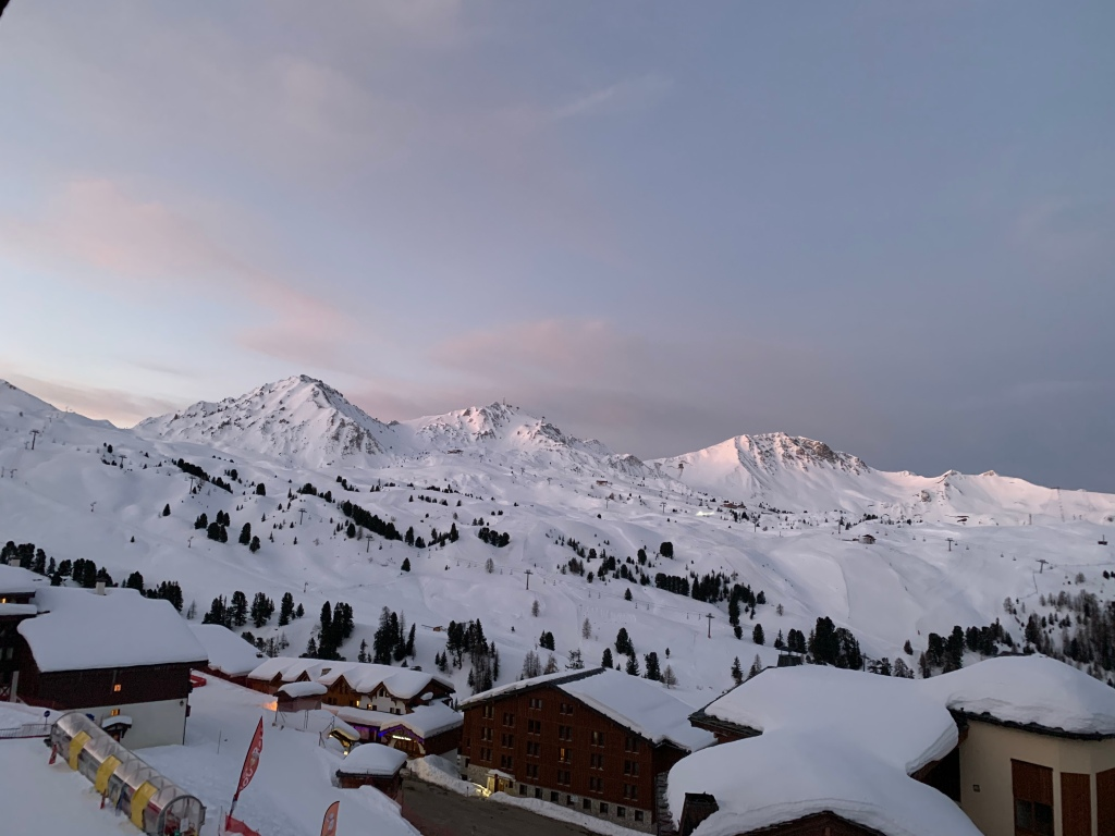 A snow filled mountain in La Plagne in France, and hotels or chalets.