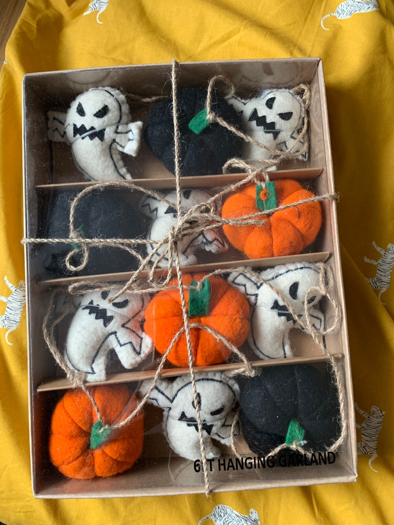 A Halloween garland that has black and orange pumpkins and a white ghost.