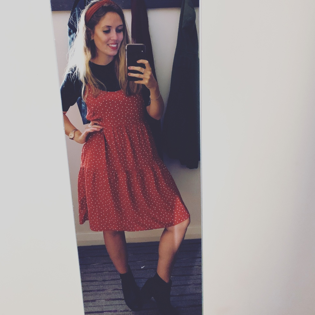A woman wearing a brown/red and white polka dot dress with a short sleeve black top underneath it. Paired with heeled black boots and a matchingmatching  headband.