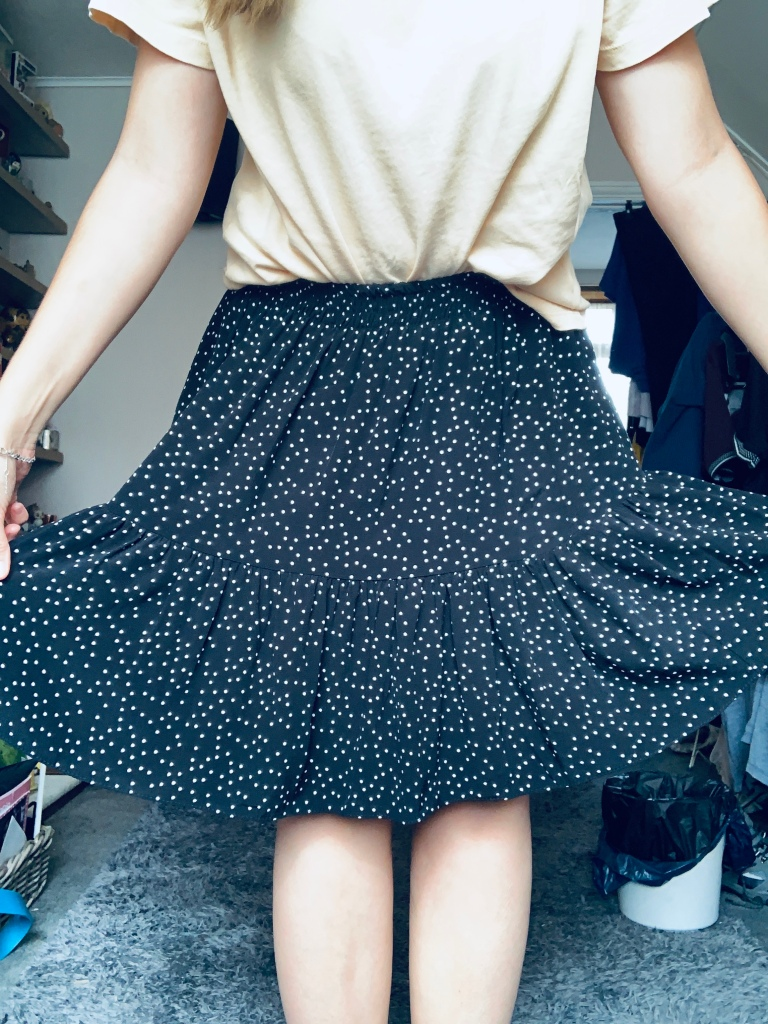 A shot of a yellow top and black and white polka dot skirt with the  persons arms holding out the sides of the skirt
