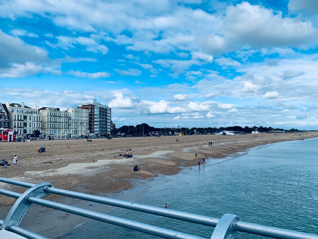 View from a pier in Portsmouth of the sea, beach and sea houses and flats/buildings