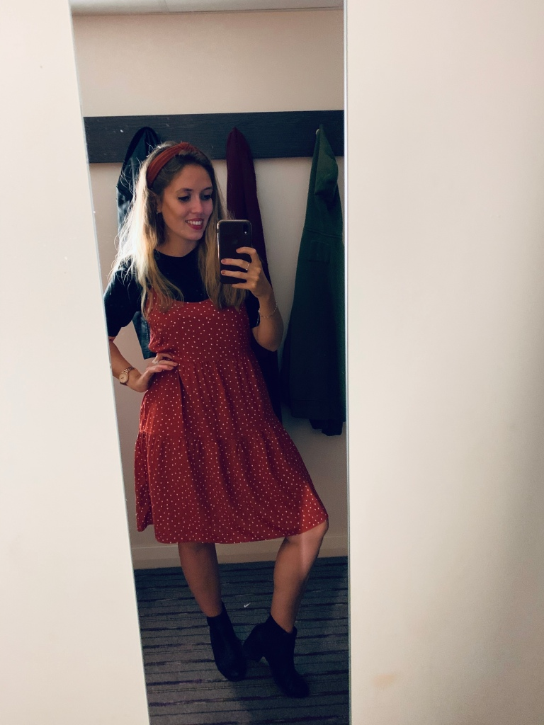 A woman taking a mirror selfie wearing a brown and white polka dot dress with a short sleeve black top underneath,  with a matching brown headband and smiling.