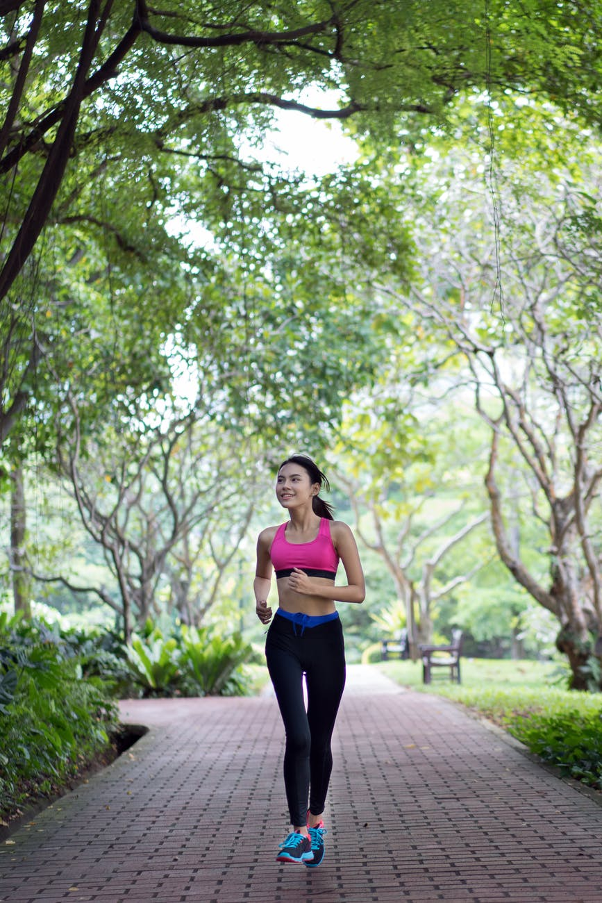 A woman running in a park on the pavement looking to the side smiling, with trees and bushes in the background.