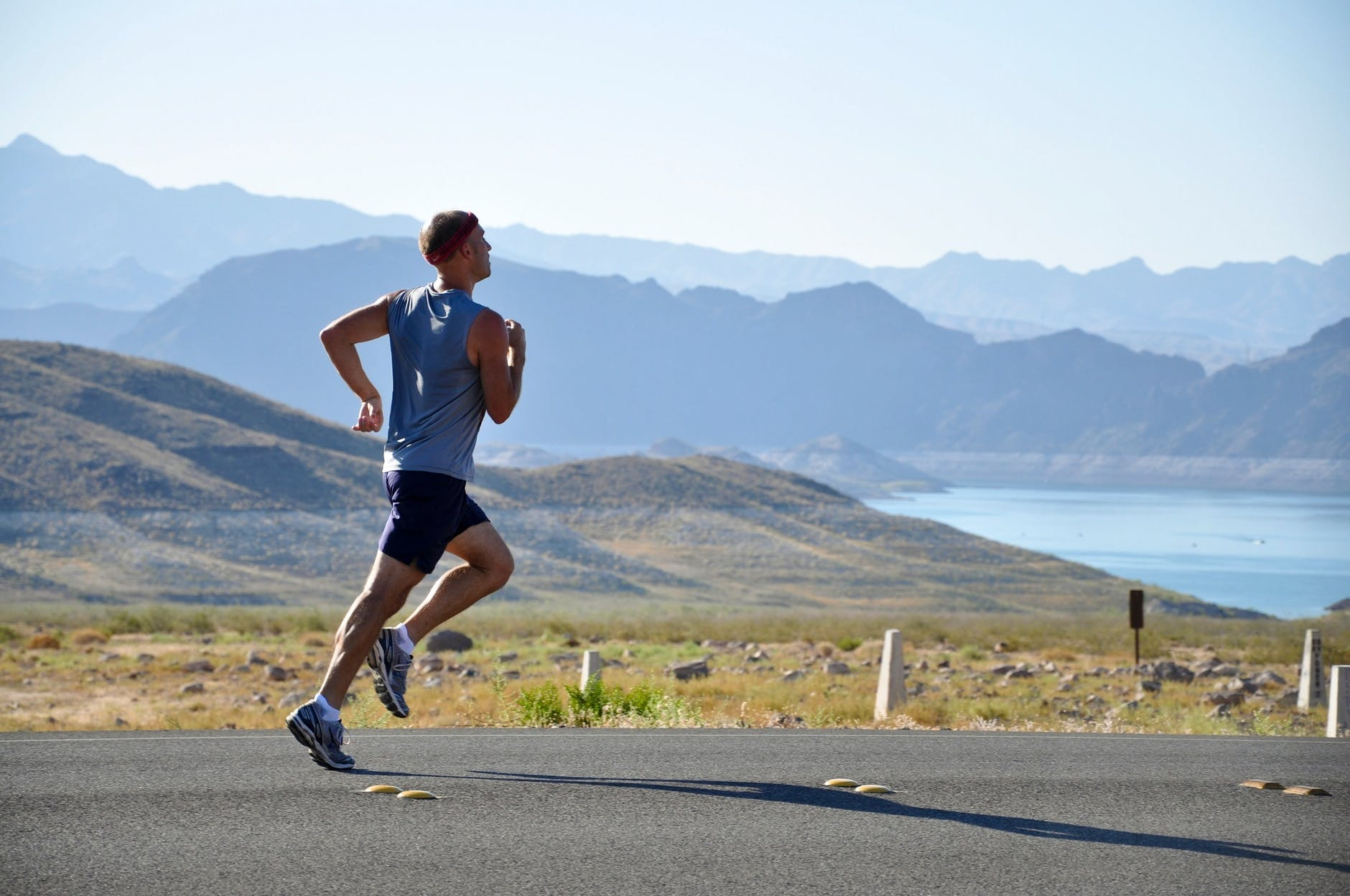 A man running on road with the mountains in the background.