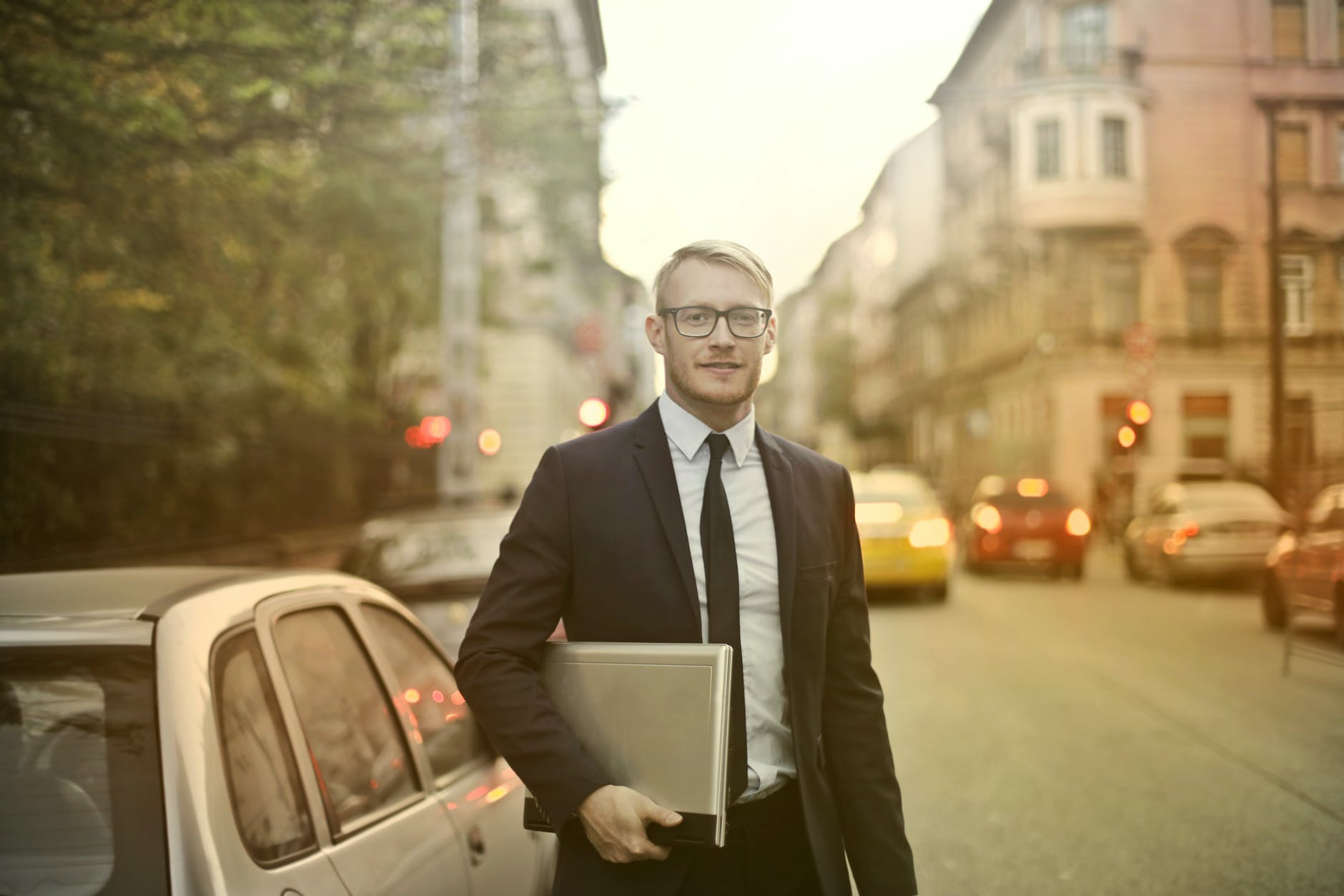 A guy in a suit holding a laptop with a blurry street in the background, whilst standing next to a silver car.