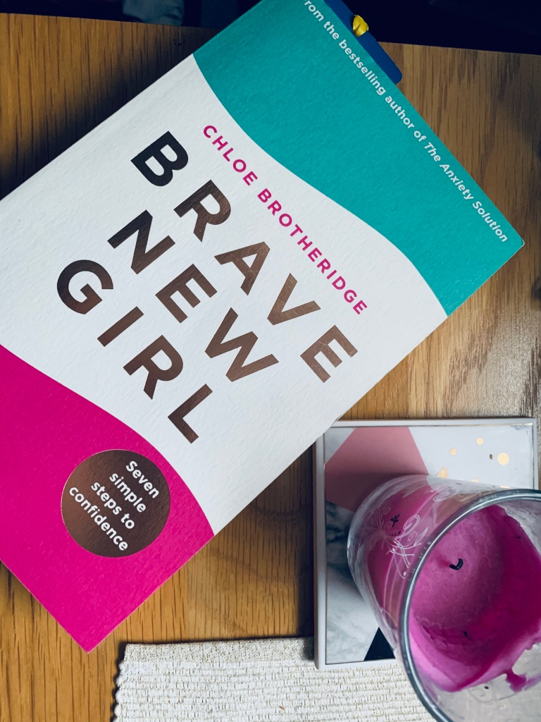"A book called ""brave new girl"" on a table next to a cup placemat."