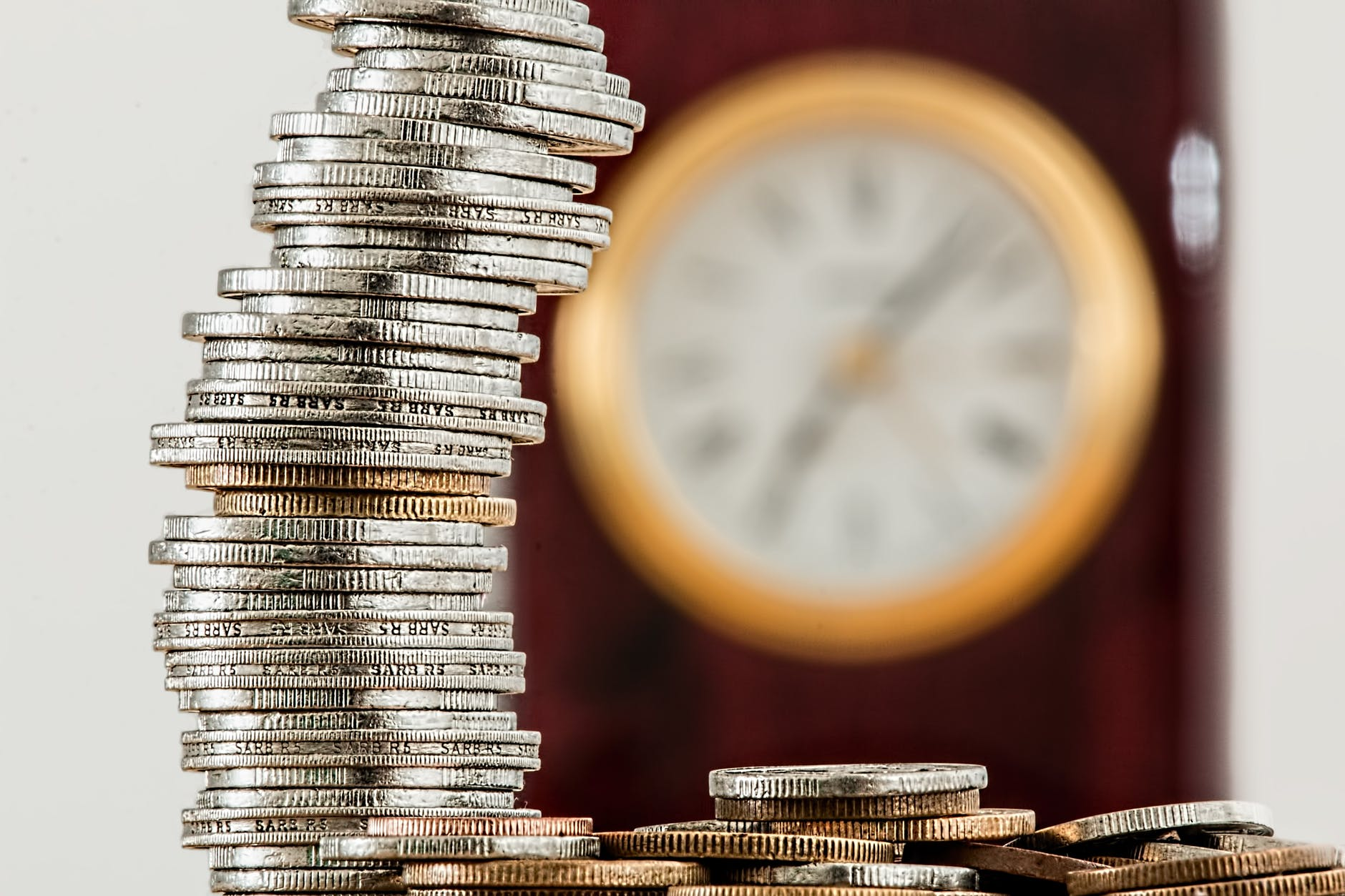 A stack of coins on top of each other with a blurry clock in the background.