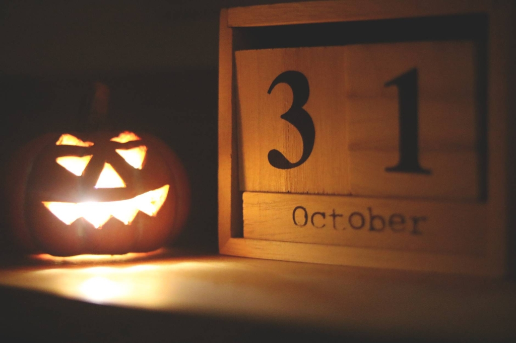 A pumpkin that is lit up next to a wooden block with 31st October on it!