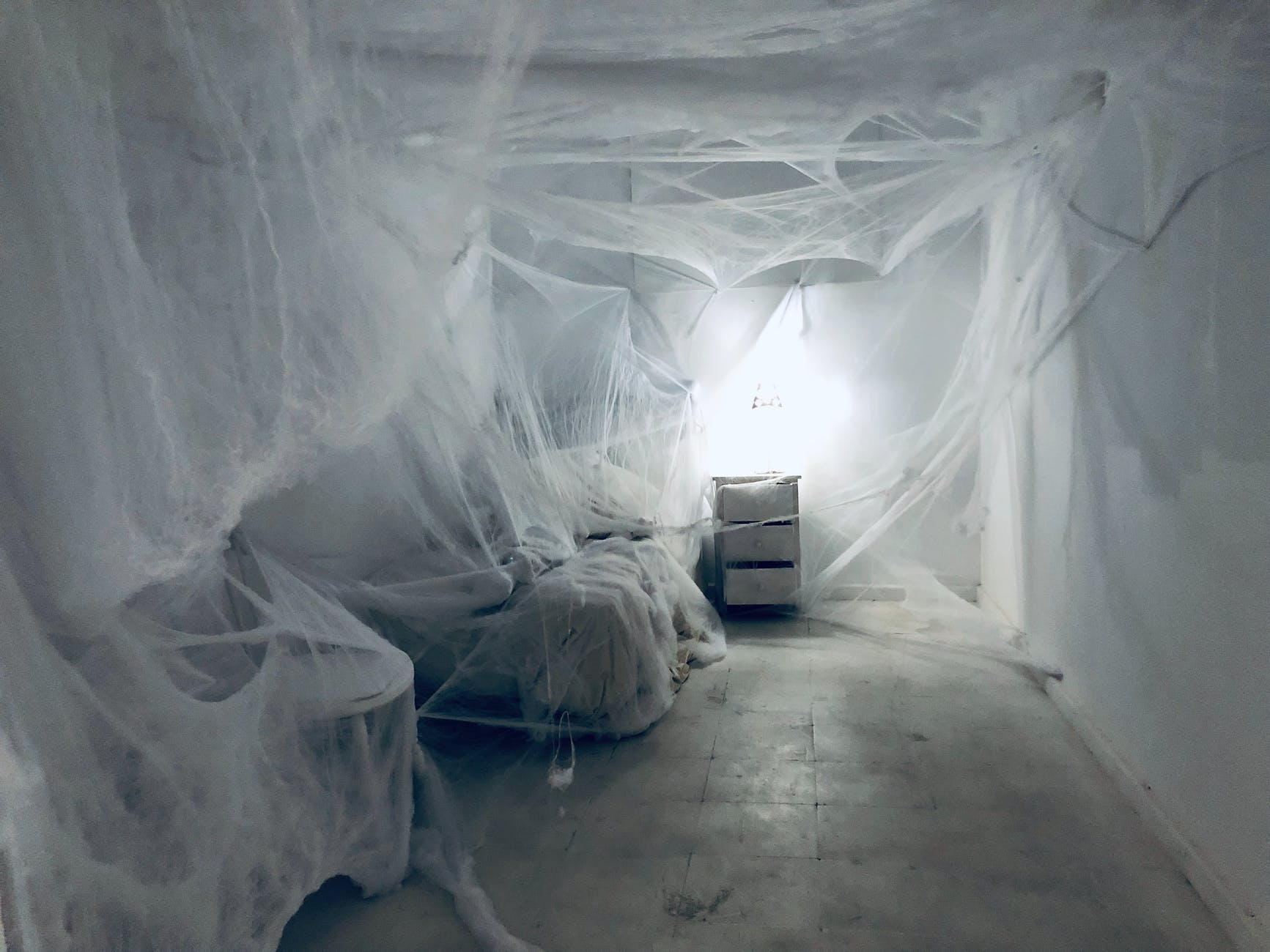 A white room filled with spider webs all around the room.