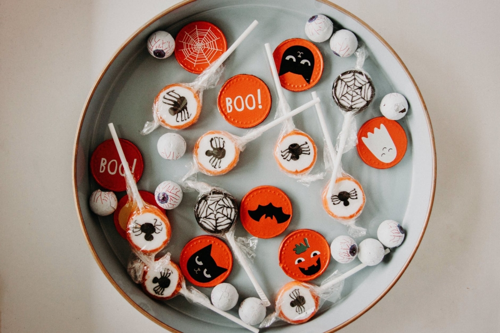"""A selection of Halloween sweets in a round deep plate. Such as lollies with spiders, cats or """"boo"""" on them, some chocolate eyeballs and Halloween chocolate coins."""