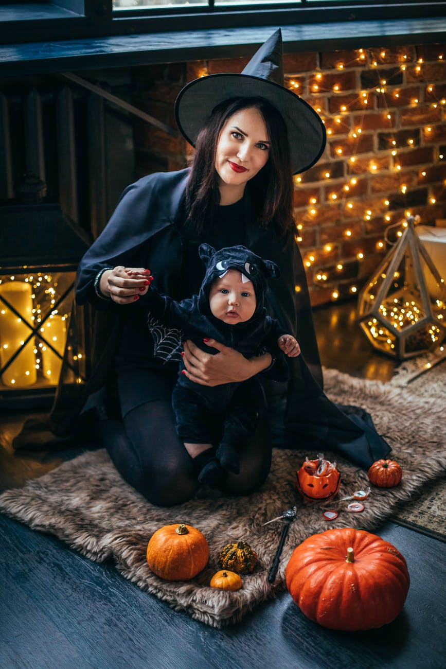 A mother dressed in a witches costume holding a baby in a black cat onesie, with fairy lights in the background, whilst they are sitting on a rug on the floor.