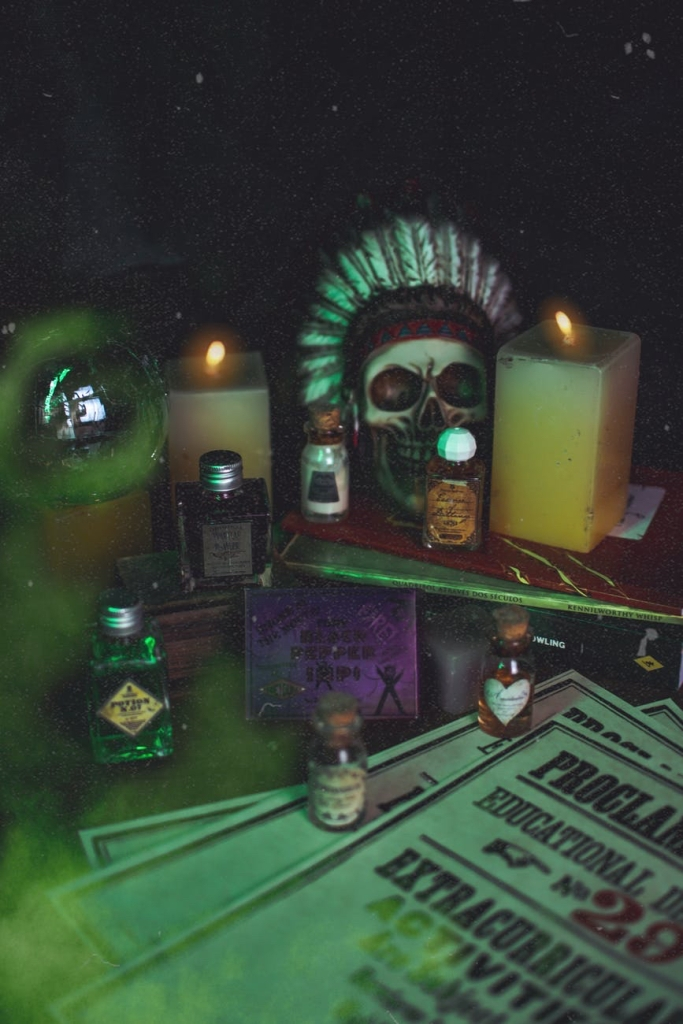 "Candles  and a selection of ""fake"" witches potions next to a skull in the dark"