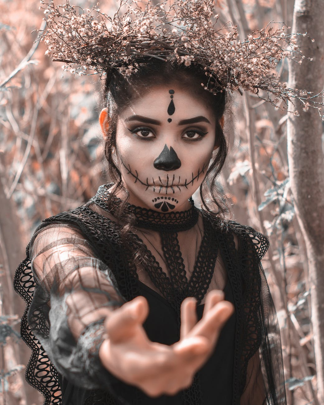 A woman with a face of make-up for Halloween, all dark and gloomy. Wearing a black lace dress and pointing to camera, and a flower headband.