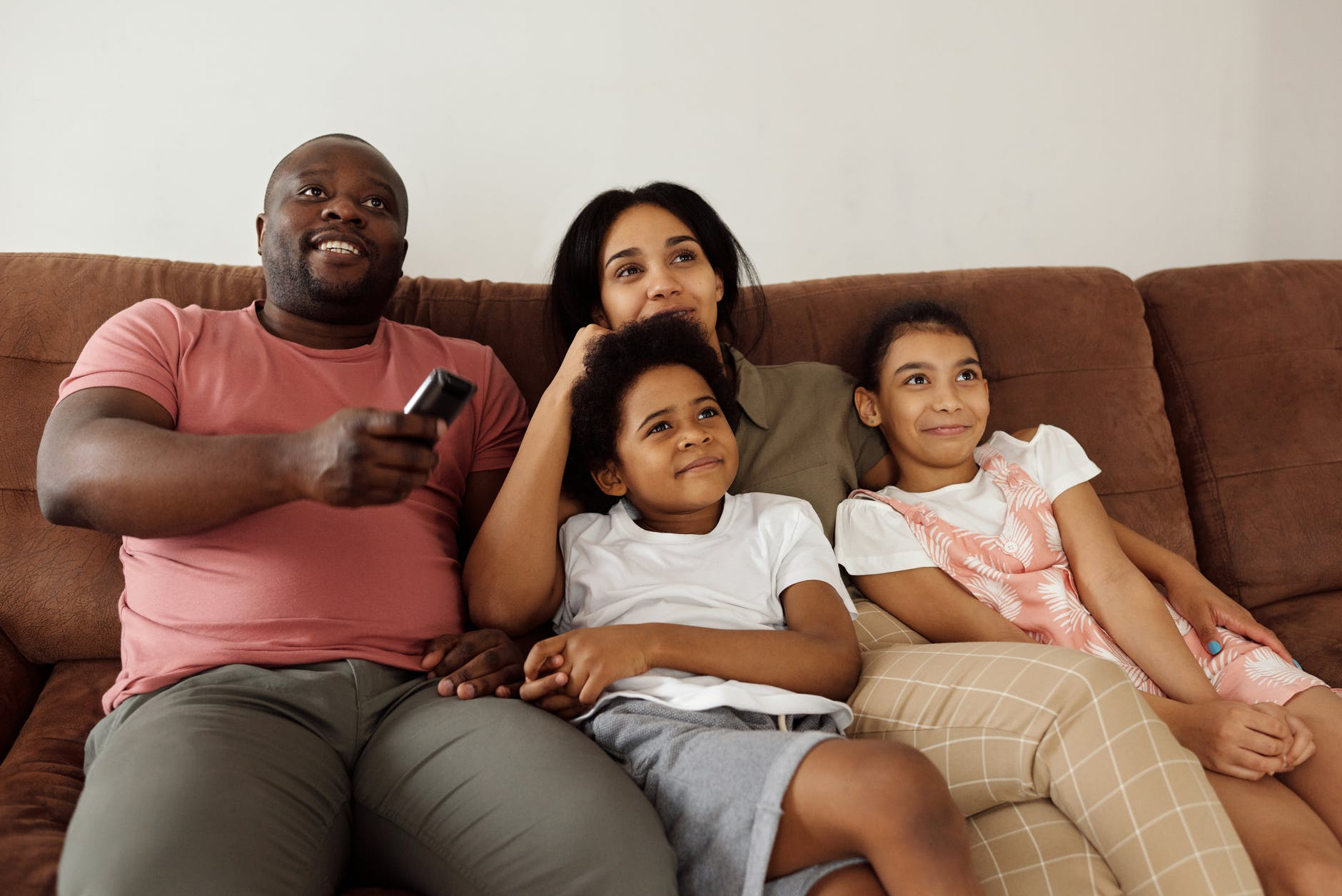 A family all sitting on a sofa watching the TV, with the dad holding the TV remote