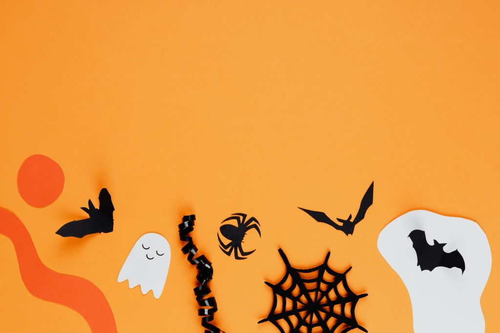 Selection of crafts for Halloween on an orange background such as ghosts, bats, spider webs.