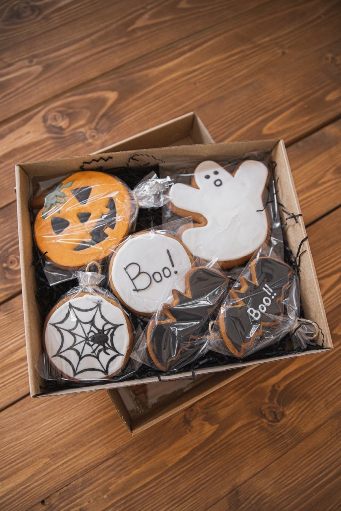 A selection of Halloween biscuits in a brown box, including bat shapes, a pumpkin, and spider webs on a round biscuit.