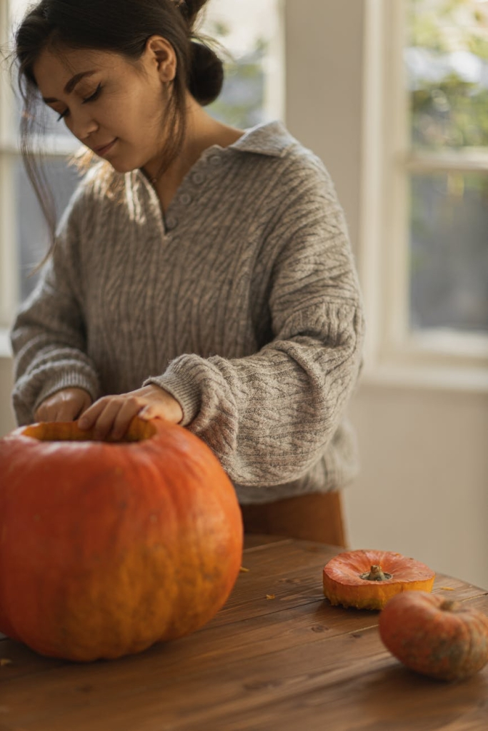 A woman carving out a giant pumpkin on the table