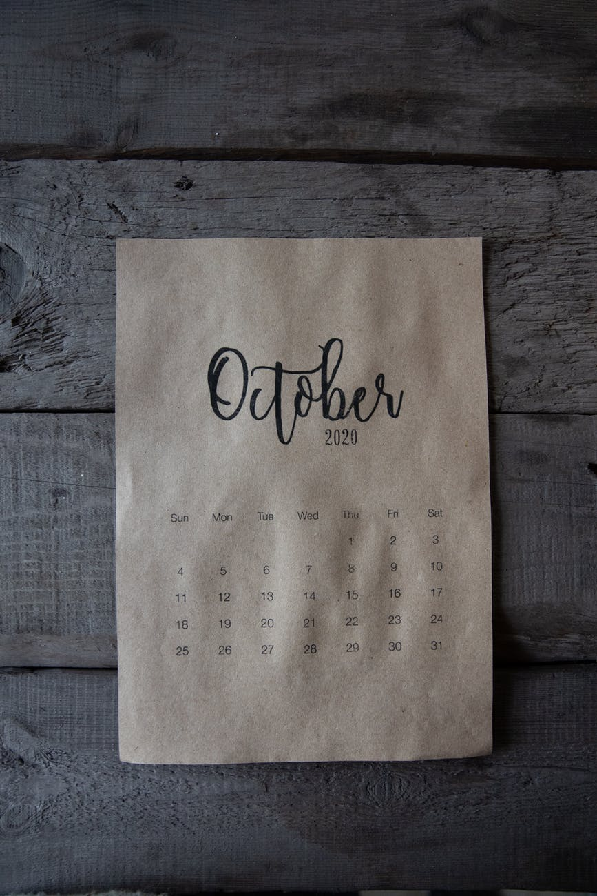 A piece of brown paper with the whole month of October on it placed onto a wooden floor.