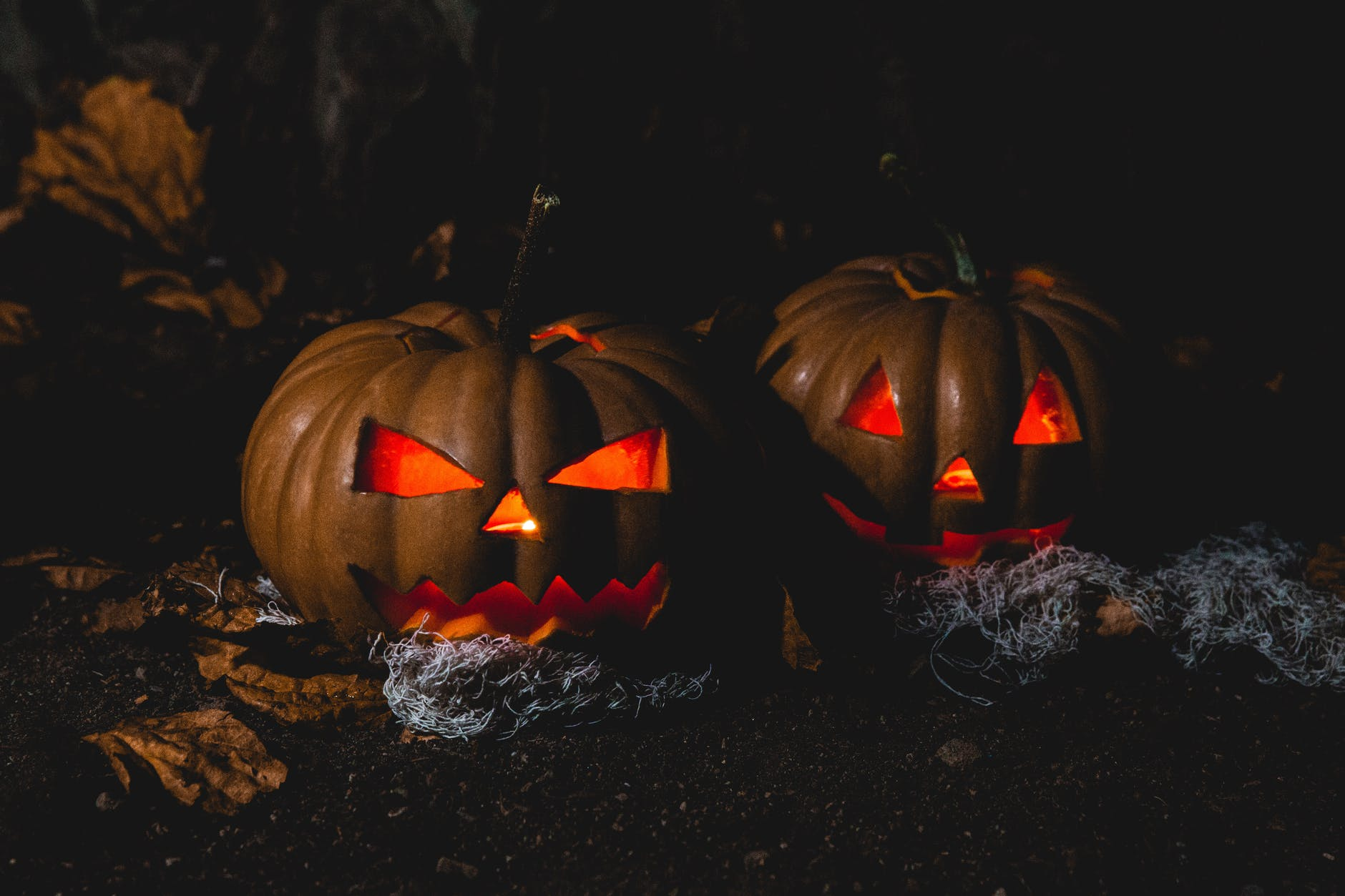Night time with two pumpkins that have been carved with a spooky face, that are both lit up laying on the ground outside.