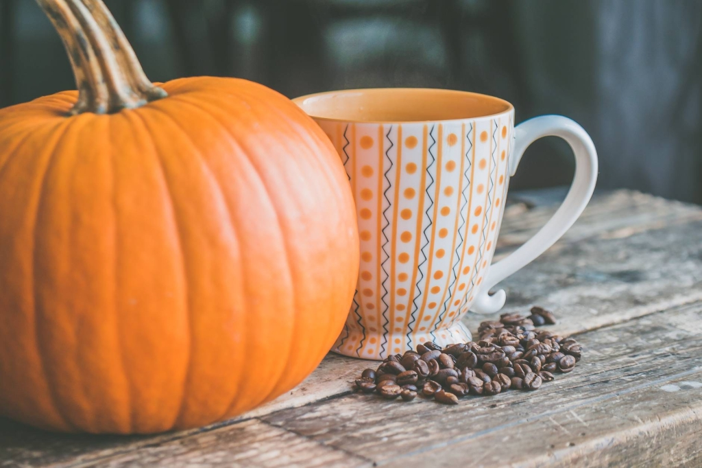 A giant orange pumpkin next to a hot drink in a mug