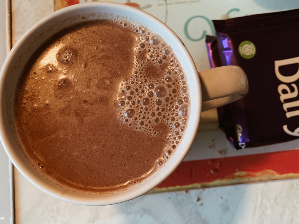 A cup filled with homemade hot chocolate next to a bar of dairy milk.