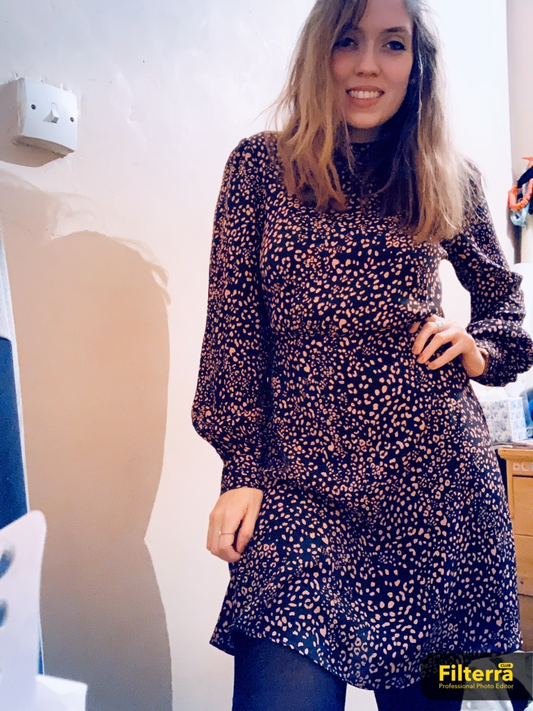A woman wearing a long sleeved black dress with pink spots all over it, whilst smiling at the camera posing in her bedroom.