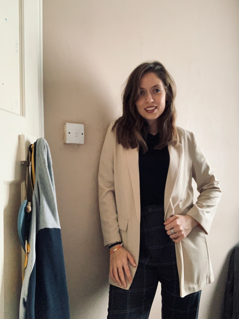 A woman standing in her room wearing a cream blazer, a black top underneath and some patterned trousers.
