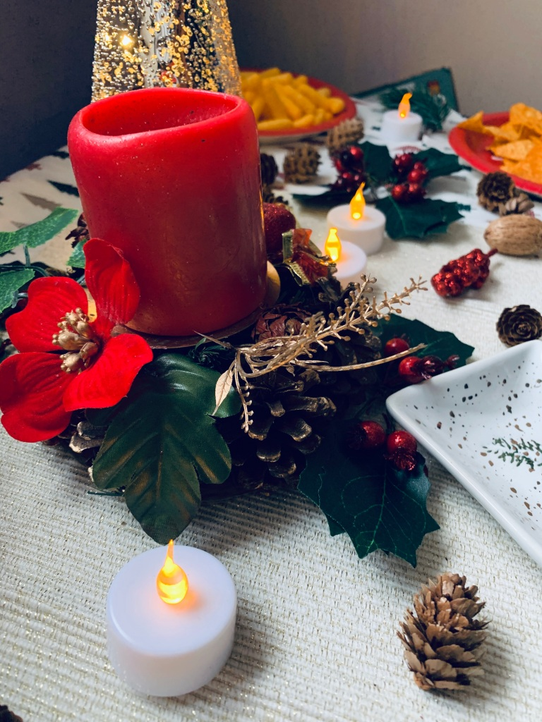 A centre piece for a festive table, with a red candle and fake leaves, pine corns and red flowers. In the background blurry other pieces of decorations such as holly, acorns and plates of food.