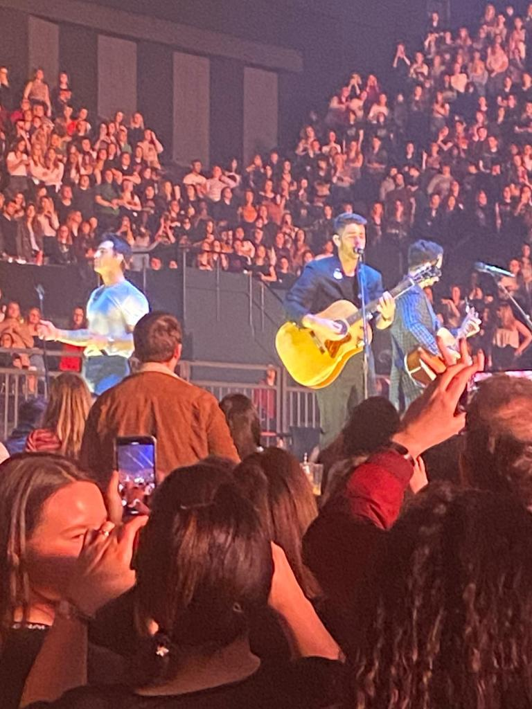 A blurry picture of the Jonas Brothers  in concert in London.