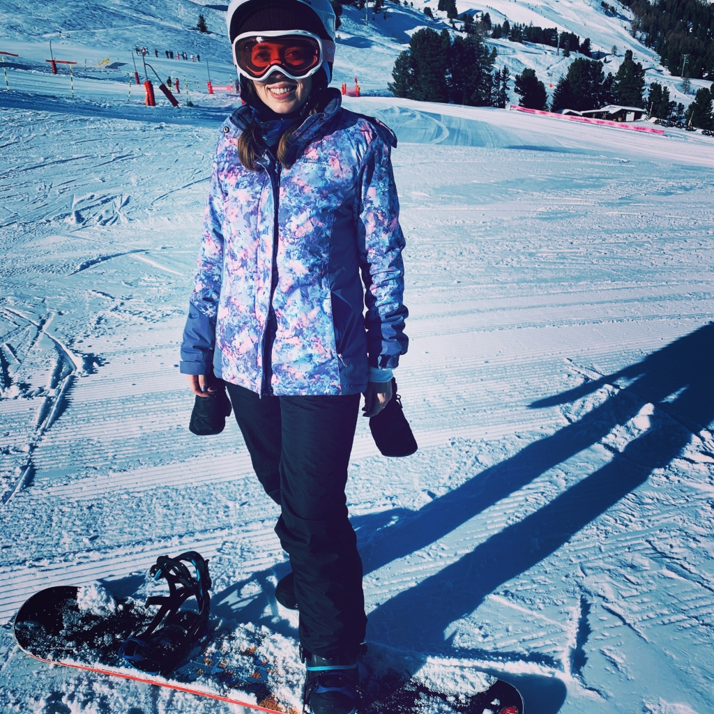 A woman with one foot strapped into a snowboard whilst on the slopes in France. In all ski gear, wearing a jacket, goggles and helmet.